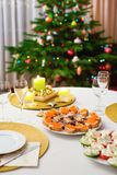 Decorated Christmas dining table. With Christmas tree in background Royalty Free Stock Photography
