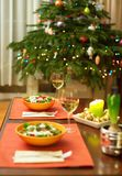 Decorated Christmas dining table. With Christmas tree in background Royalty Free Stock Image