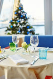 Decorated Christmas dining table. With wine glasses and christmas tree in background Stock Image