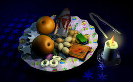 Decorated Christmas dish with fruit and sweets, beside a candle Stock Photo