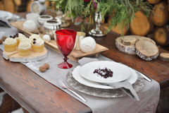 Decorated Christmas holiday table ready for dinner. Beautifully set with candles, spruce twigs, plates and serviettes Royalty Free Stock Photos