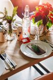 Decorated Christmas holiday table ready for dinner. Beautifully decorated table set with candles, spruce twigs, plates. And serviettes for event in the Stock Image