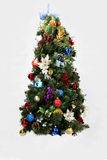 Decorated Christmas tree. Closeup of colorfully decorated artificial Christmas tree isolated on white background Stock Images