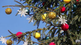 Decorated Christmas tree on background blue sky. Beautiful, big, tall, decorated Christmas tree with Christmas toys, balls, garlands and various ornaments stands stock video footage