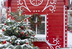 Decorated Christmas tree on the background of a red fairytale house royalty free stock image