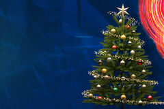 Decorated Christmas Tree on Blue Background with Copy Space. A decorated Christmas tree against a blue background with copy space Royalty Free Stock Image