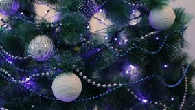 Decorated Christmas tree with blue lights. White Christmas ball and garland.  stock video footage