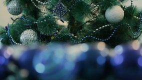 Decorated Christmas tree with blue lights. White Christmas ball and garland. Unfocused image in the foreground.  stock video