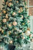 Closeup of red bauble hanging from decorated Christmas tree. Retro filter effect Royalty Free Stock Photo