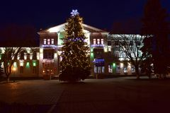 Decorated Christmas tree in the central square of the city. Decorated natural Christmas tree in the central square of the city in the late evening stock photos