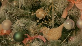 Decorated Christmas tree. Christmas tree decorated with balls, soft toys, birds and artificial snow, ribbons, poured in the light of garlands stock video footage
