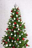 Decorated christmas tree with colorful balls over white brick wa Royalty Free Stock Photo