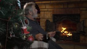 Decorated Christmas tree with elderly man near fireplace on the background stock video footage