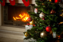 Decorated Christmas tree in front of burning fireplace at house. Stock Image