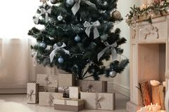 Decorated Christmas tree with gift boxes. And fireplace in stylish living room interior Stock Image