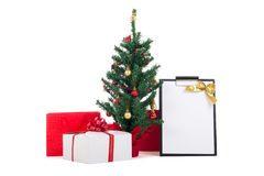 Decorated christmas tree, gift boxes and gift list on white back Stock Images