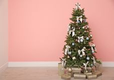 Decorated Christmas tree with gift boxes. Indoors Royalty Free Stock Images