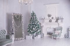 Decorated Christmas tree and gift boxes in living room.large white living room with a vintage furniture and a large stock images
