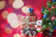 Decorated christmas tree with gift boxes and Santa Claus toy. With blurred and sparkling bokeh at abstract background. Concept of family gifts and presents at stock photo