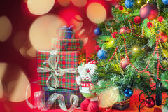 Decorated christmas tree with gift boxes and Santa Clus toy. With blurred and sparkling bokeh at abstract background. Concept of family gifts and presents at stock photos