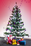 Decorated Christmas tree with gifts around and with the lit cand Royalty Free Stock Photography