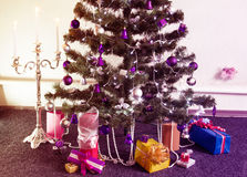Decorated Christmas tree with gifts around and with the lit cand Royalty Free Stock Image