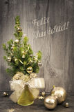 Decorated Christmas tree and golden baubles on wood, caption Royalty Free Stock Photography