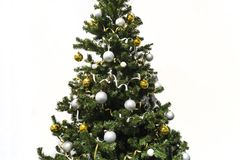 Decorated Christmas tree isolated on white background. Christmas tree decorated with yellow and white balls and tinsel.  stock images