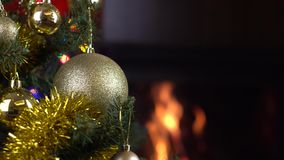 Decorated christmas tree with lights in front of fireplace. Christmas tree with decorations and lights in front of fireplace stock video footage
