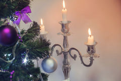 Decorated Christmas tree and lit white candlesticks Royalty Free Stock Photos