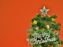 Decorated Christmas tree with Merry Christmas sign on red wall background. Stock Images