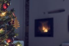 Decorated Christmas tree near a burning fire. Decorated Christmas tree in front of a burning fire in a wall insert in the darkness of Christmas Eve in a cosy Stock Photos