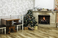 Decorated Christmas tree near fireplace Stock Image