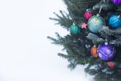 A decorated Christmas tree outside with colorful baubles made of glass stock photo
