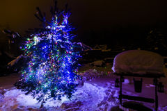 Decorated christmas tree outside with lights covered with snow Royalty Free Stock Photo
