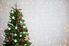 Decorated christmas tree over white brick wall with lights Stock Images