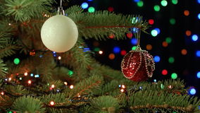 Decorated Christmas tree red and white orbs on a dark background with garland stock footage