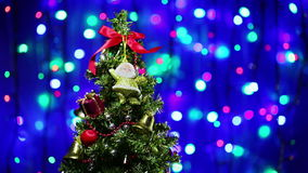 Decorated Christmas tree rotating on blinking background. Decorated Christmas tree rotating on blinking multicolor bokeh background stock footage