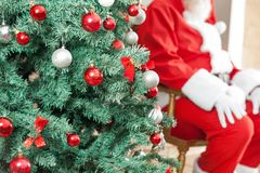 Decorated Christmas Tree With Santa Claus Sitting Royalty Free Stock Photography