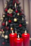 Decorated christmas tree with three candles. Decorated christmas tree with gold, red balls and three candles royalty free stock image