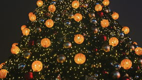Decorated Christmas tree in toys for Christmas in Moscow on the street. Glowing golden balls and garlands on the stock video footage