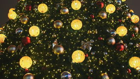 Decorated Christmas tree in toys for Christmas in Moscow on the street. Glowing golden balls and garlands on the stock video