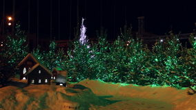 Decorated christmas trees and miniature houses. In the town square by night stock footage