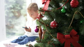 Decorated Christmass tree and little girl with smart phone on the background. stock video footage