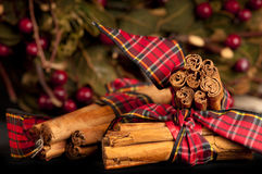 Decorated Cinnamon sticks for Christmas. Warm glowing cinnamon sticks wrapped in tartan ribbon for Christmas with red berries in the background Stock Photos