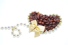 Decorated coffee. Beans in gold heart with bow Royalty Free Stock Image