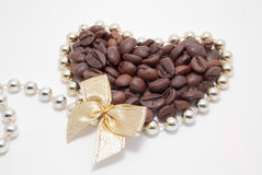 Decorated coffee. Beans in gold heart with bow isolated on white. do you love coffee Royalty Free Stock Photo