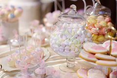 Decorated colorful candies on a pink table Royalty Free Stock Photos