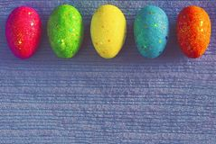 Decorated colorful Easter eggs on blue knitted background with space for text. Trendy minimal pop art style and colors. royalty free stock photos