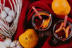 Decorated composition of mugs with mulled wine in knitted scarf, close up stock photos